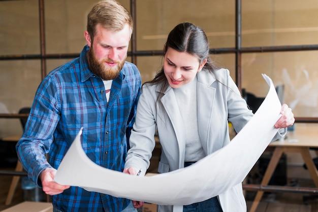 Empresários profissionais a trabalhar na impressão azul a sorrir Foto gratuita