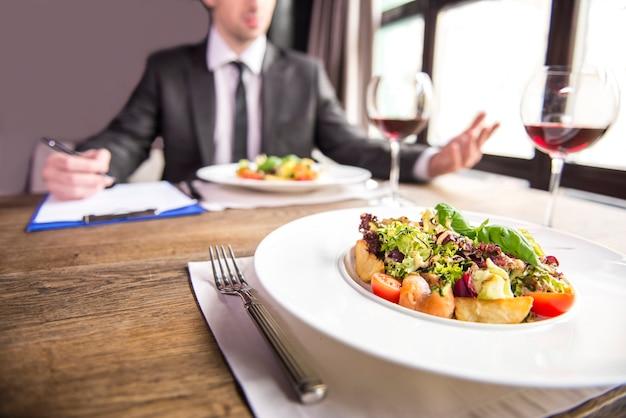 Empresários que trabalham com documentos durante um almoço de negócios. Foto Premium