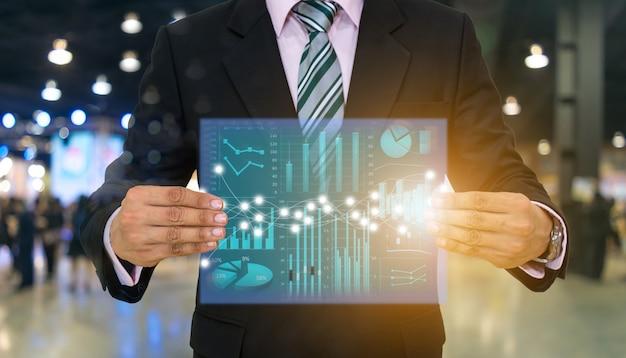 Empresários segurar a tecnologia financeira de tela e gráficos de investimento Foto Premium
