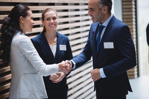 Empresários tendo uma discussão e apertando as mãos Foto gratuita
