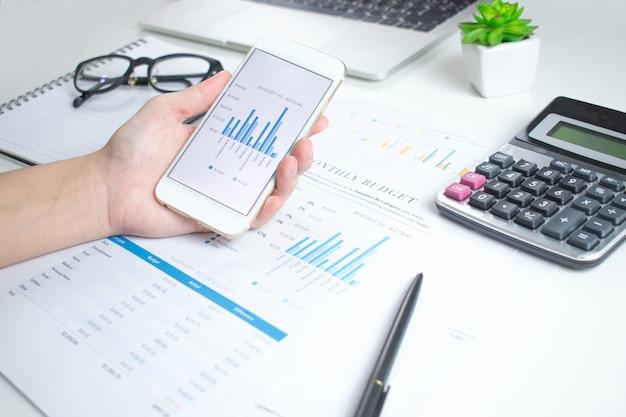 Empresários usam smartphones para calcular gráficos financeiros em uma mesa branca. Foto Premium