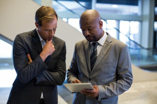 Empresários usando tablet digital Foto gratuita