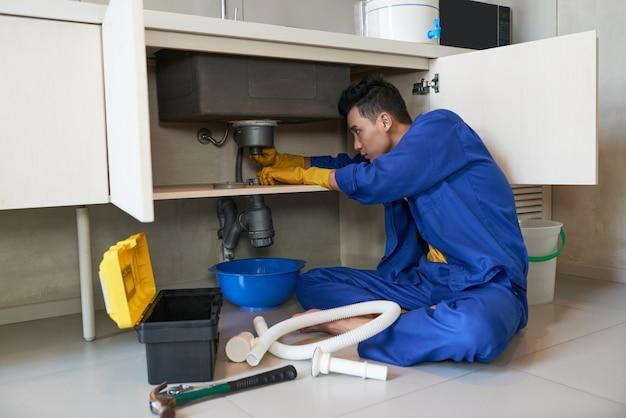 Encanador asiático de macacão azul, limpando o bloqueio no ralo Foto gratuita