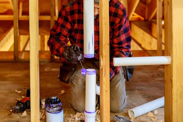 Encanador colocando cola no tubo de drenagem de pvc da área de trabalho. Foto Premium