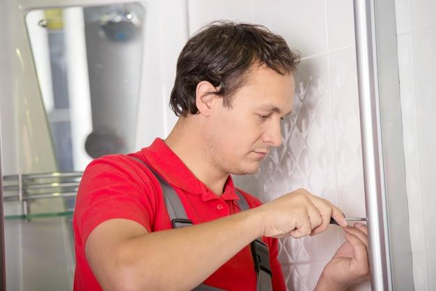 Encanador consertando um chuveiro no quarto. Foto Premium