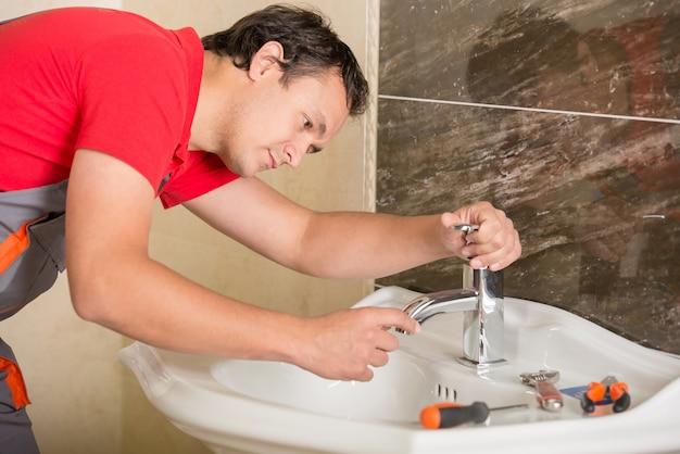 Encanador está consertando uma torneira com água no banheiro Foto Premium