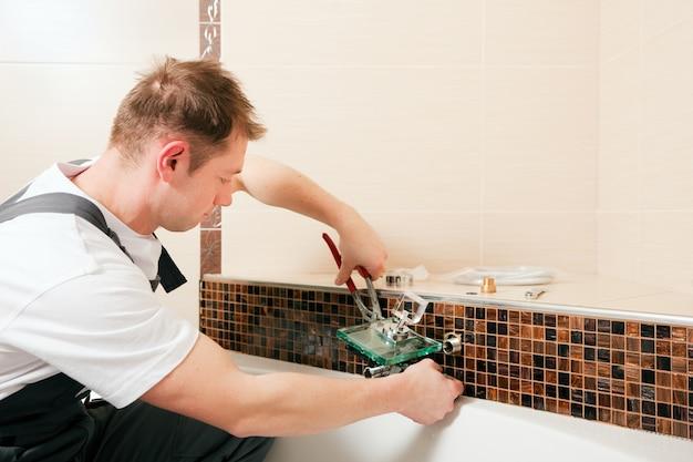 Encanador instalar uma torneira misturadora em um banheiro Foto Premium