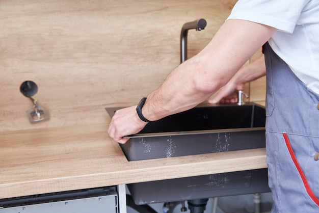 Encanador masculino instala pia na cozinha Foto Premium