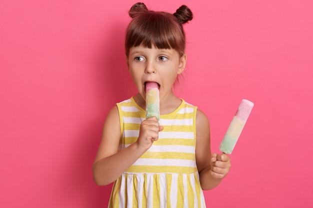 Encantadora criança do sexo feminino mordendo sorvete de água e olhando de lado, garota com dois nós, usando vestido de verão, posando isolado sobre fundo rosa, fica com sorvetes nas mãos. Foto gratuita