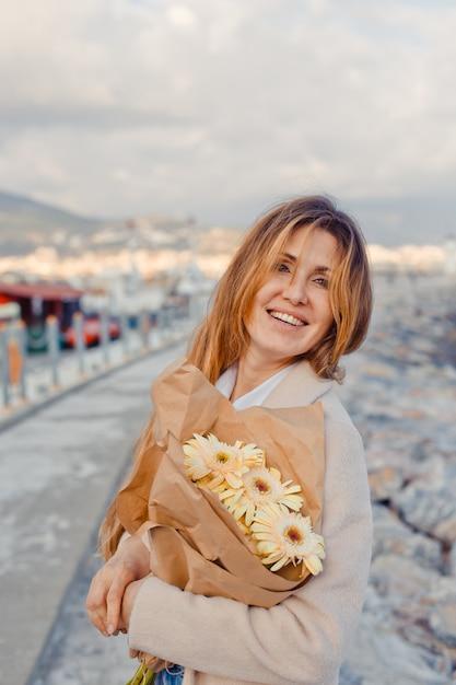 Encantadora dama em pé sorrindo com flores na beira-mar durante a tarde ee olhando alegre. Foto gratuita