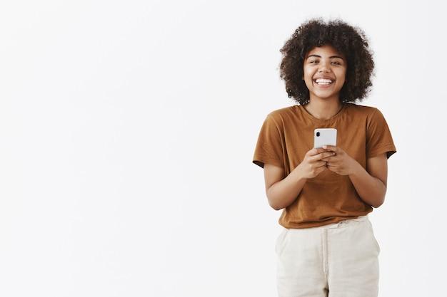 Encantadora e simpática adolescente afro-americana com cabelo encaracolado, vestida com estilo, segurando um smartphone e sorrindo amplamente Foto gratuita