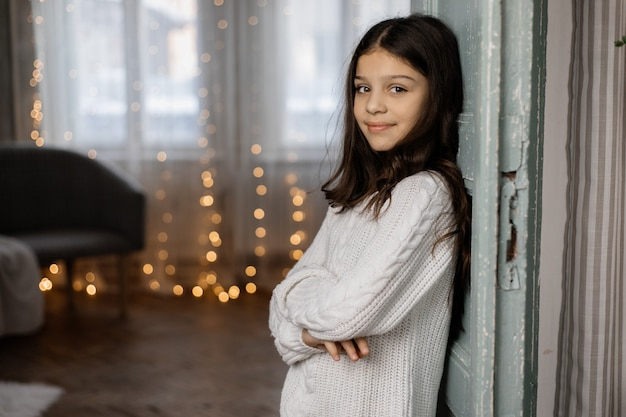 Encantadora jovem adolescente na camisola branca e calça jeans coloca na sala com decoração de natal Foto gratuita