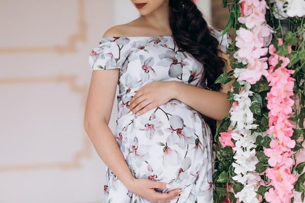 Encantadora jovem grávida posa em um estúdio com flores cor de rosa Foto gratuita