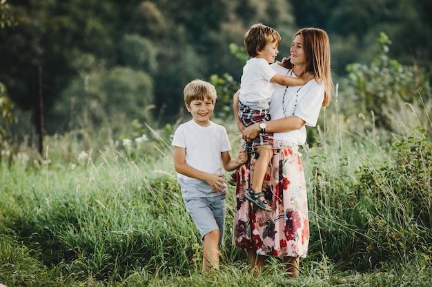 Encantadora jovem mãe caminha junto com seus filhos pequenos Foto gratuita