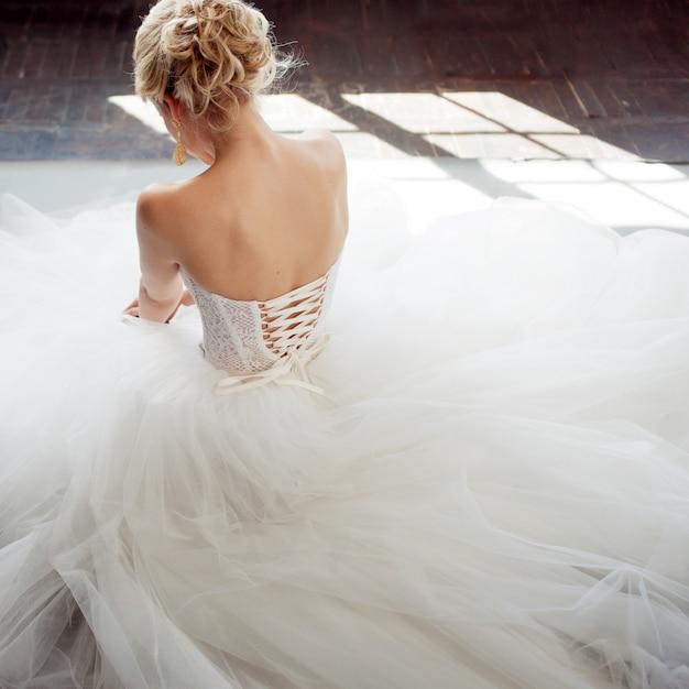 Encantadora jovem noiva vestido de noiva luxuoso. menina bonita de branco. fundo cinza. de volta Foto Premium