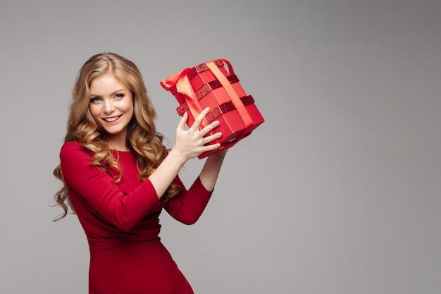 Encantadora menina feliz com caixas vermelhas com laço vermelho. Foto Premium