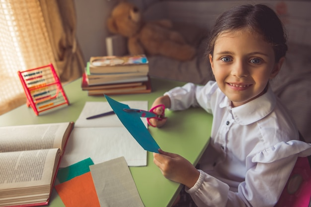 Encantadora menina na escola uniforme está cortando papel. Foto Premium
