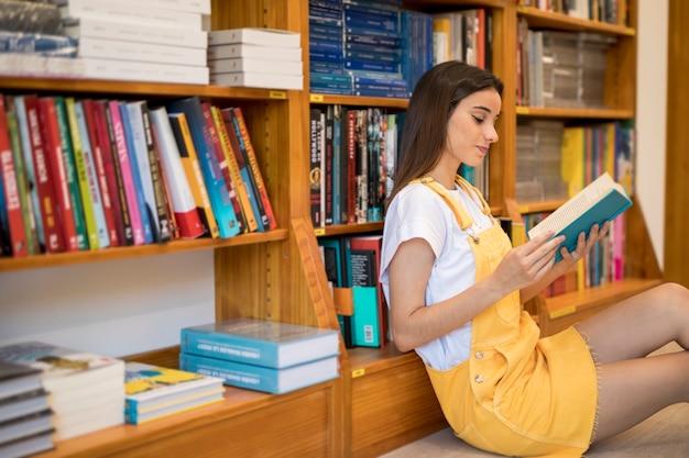 Encantadora mulher jovem sentado na biblioteca e lendo o livro Foto gratuita