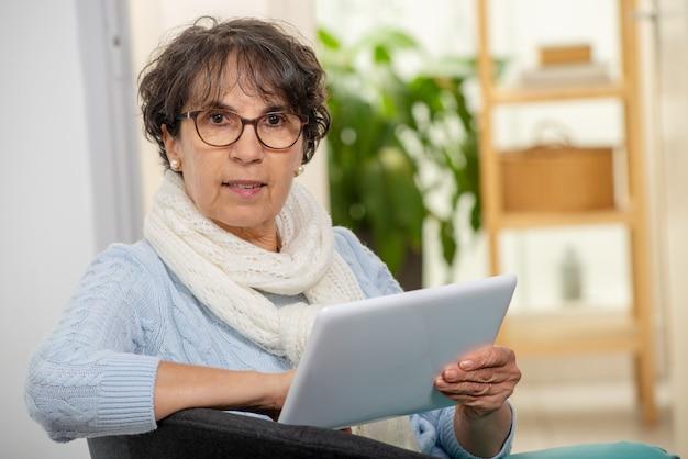 Encantadora mulher morena sênior com óculos usando tablet digital em casa Foto Premium