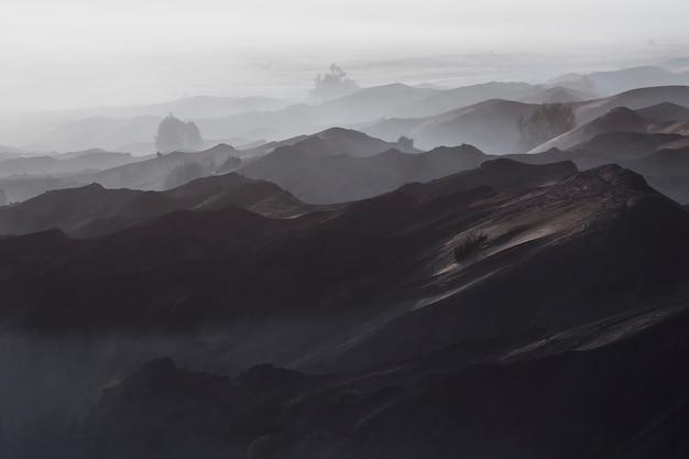 Encantadora vista do deserto de bromo em uma manhã de nevoeiro vista do monte bromo Foto Premium