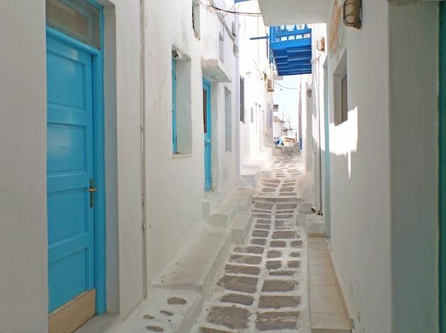Encantadores edifícios brancos e azuis com pequeno beco levando a moinhos de vento de chora, mykonos, grécia Foto Premium