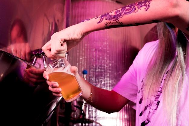 Enchendo cerveja em vidro Foto gratuita