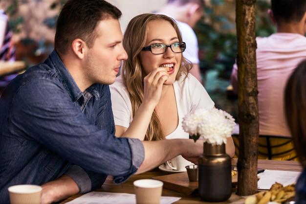 Encontro duplo com melhores amigos e atmosfera acolhedora no pequeno café local tranquilo Foto gratuita