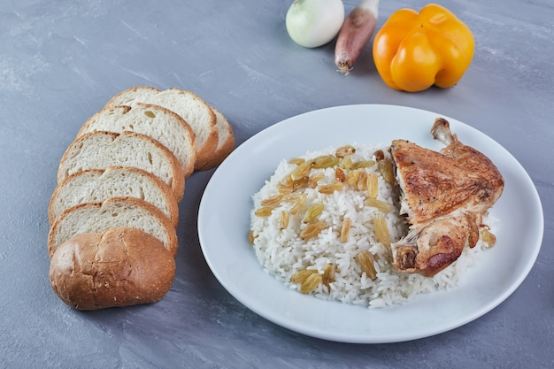 Enfeite de arroz com sultana e frango frito em um prato branco com pão. Foto gratuita