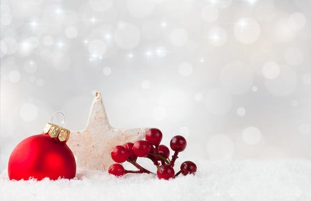 Enfeite de natal vermelho e bagas de arbusto de azevinho e uma estrela branca em uma superfície de neve Foto gratuita