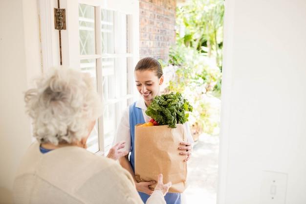 Enfermeira agradável trazer legumes ao paciente idoso em casa Foto Premium