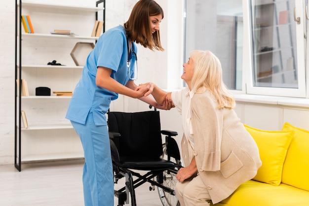Enfermeira, ajudando, mulher velha, levantar-se Foto gratuita
