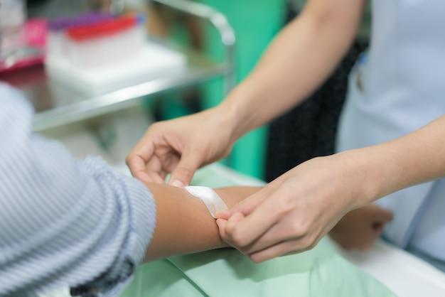 Enfermeira aplicar curativo na mão do paciente após o exame de sangue no hospital. Foto Premium