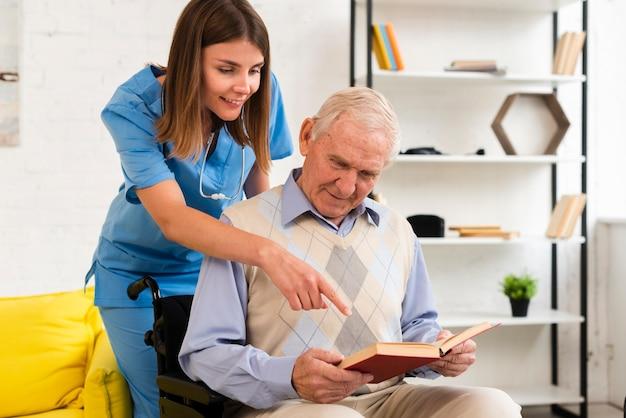 Enfermeira apontando para o livro do velho Foto gratuita