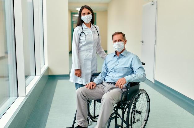 Enfermeira caucasiana, cuidando de um paciente adulto do sexo masculino, sentado em uma cadeira de rodas no hospital. mulher jovem e velho usando máscara cirúrgica para se proteger contra a pandemia covid 19. Foto Premium