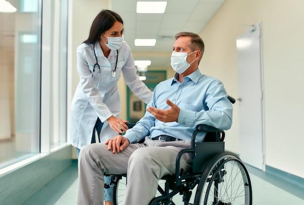 Enfermeira caucasiana, cuidando de um paciente adulto do sexo masculino, sentado em uma cadeira de rodas no hospital. Foto Premium