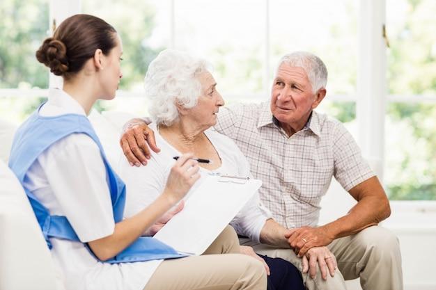 Enfermeira cuidando de pacientes idosos doentes em casa Foto Premium