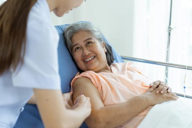 Enfermeira da mão segurando o comprimido para injetar para pacientes idosos do sexo feminino deitado na cama com sorrindo, cópia espaço, saudável e conceito médico Foto gratuita