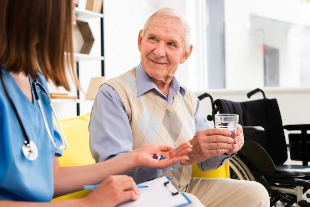 Enfermeira, dar, pílulas, para, smiley, homem velho Foto gratuita