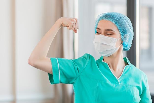 Enfermeira de baixo ângulo mostrando os músculos Foto gratuita