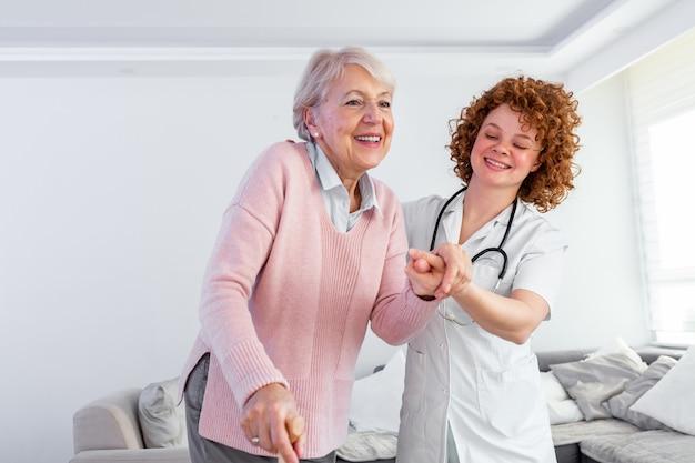 Enfermeira de sorriso que ajuda a senhora superior a andar em torno do lar de idosos. Foto Premium