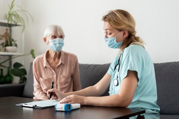 Enfermeira e idosa durante um check-up em uma casa de repouso Foto gratuita
