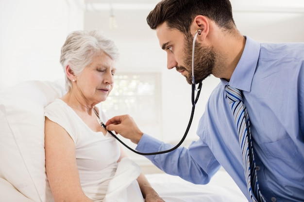 Enfermeira em casa ouvindo o peito do paciente com estetoscópio em casa Foto Premium