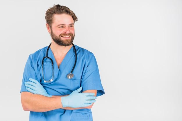 Enfermeira homem cruzando as mãos e desviar o olhar Foto gratuita