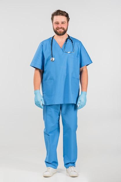 Enfermeira homem de pé e sorrindo Foto gratuita