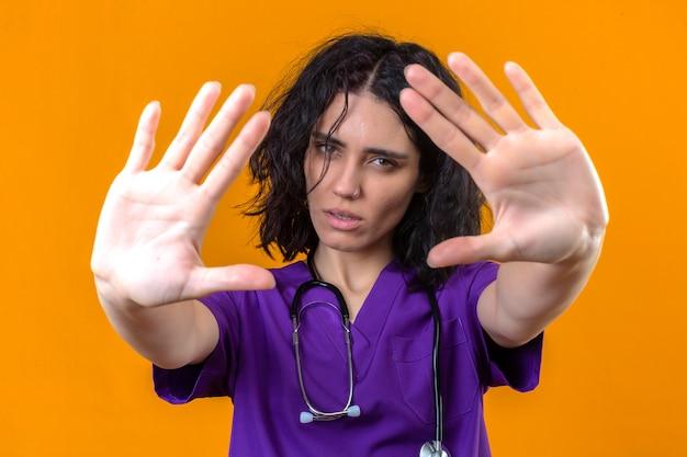 Enfermeira jovem com uniforme médico e estetoscópio em pé com as mãos abertas, fazendo sinal de pare com gesto de defesa de expressão sério e confiante Foto gratuita
