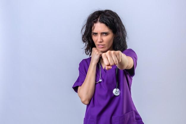 Enfermeira jovem em uniforme médico e com estetoscópio em pé, pronta para lutar com o punho gesto de defesa cara zangada e chateada Foto gratuita