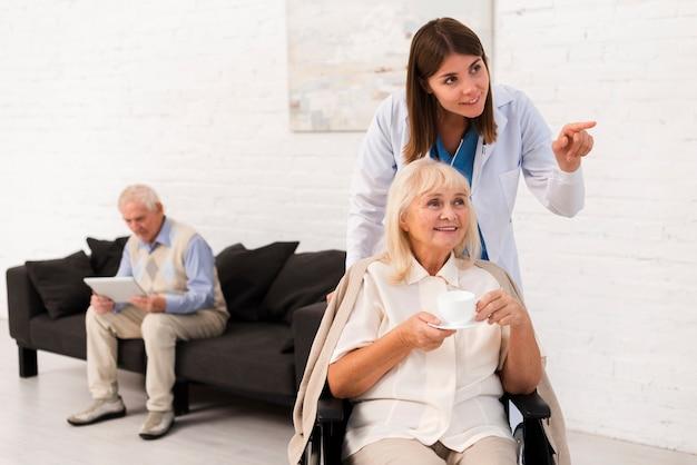 Enfermeira mostrando a velhinha algo Foto Premium