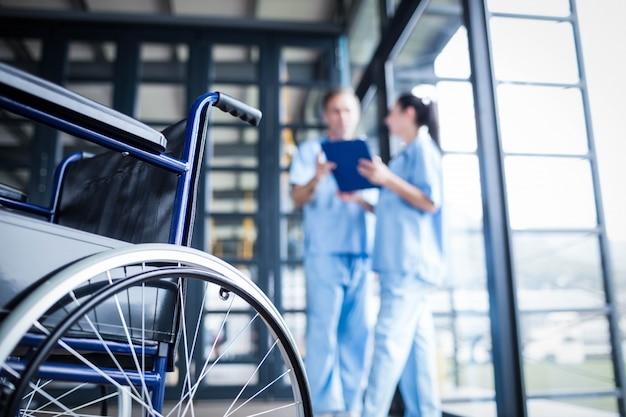 Enfermeira pessoal trazendo uma cadeira de rodas no hospital Foto Premium