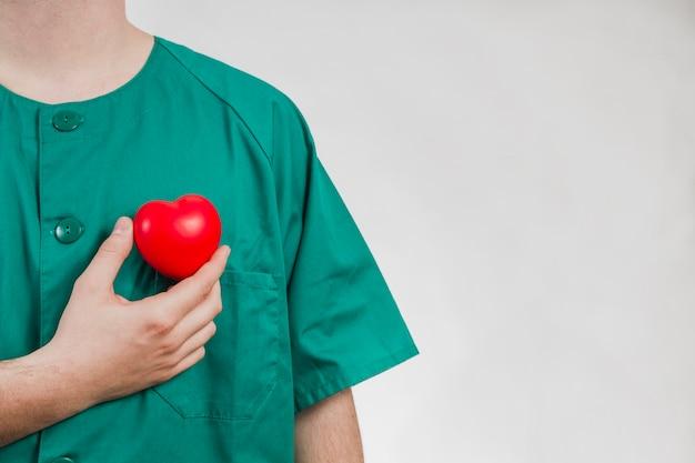 Enfermeira que mostra o coração de plástico Foto gratuita