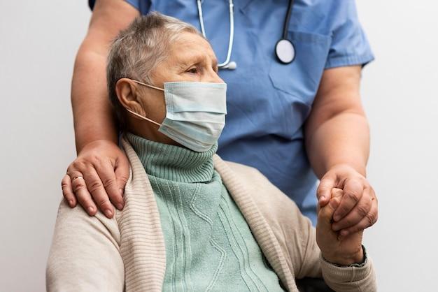 Enfermeira segurando a mão de uma mulher sênior em uma casa de repouso Foto Premium